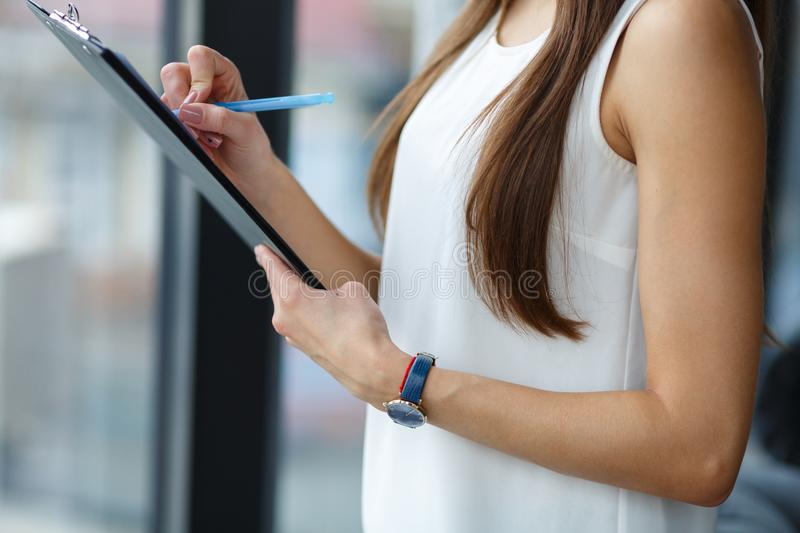 Young brunette holding clipboard and pen. Business woman. royalty free stock photo