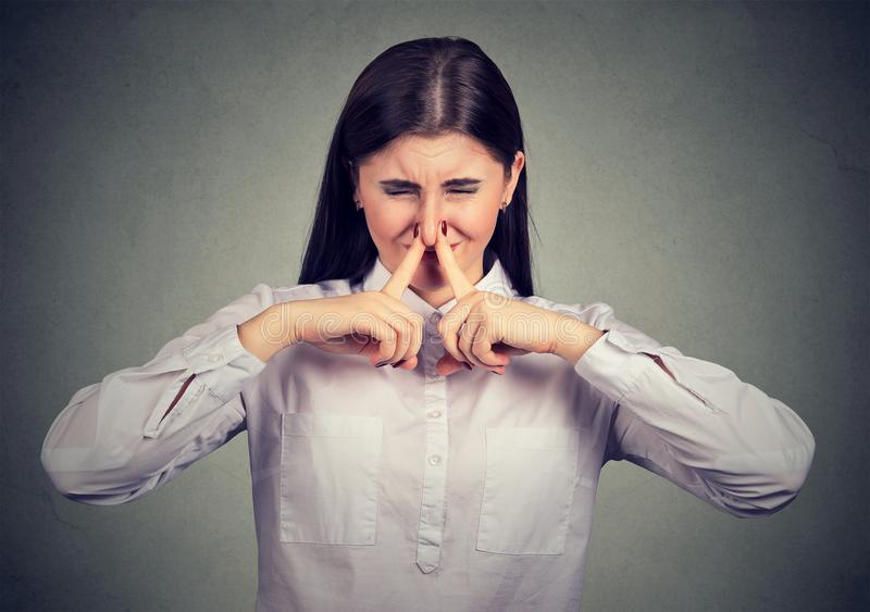 Woman suffering from bad smell. Young brunette holding her nose and squeezing eyes disliking bad smell stock photography