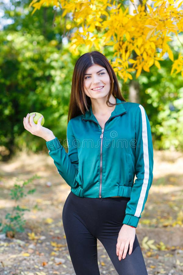 A young girl in a sports suit holds a green apple outdoors. Beautiful sports woman eating fruits. royalty free stock photography
