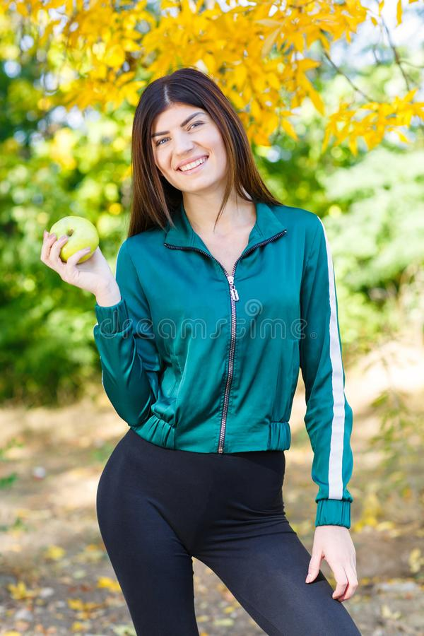 A young girl in a sports suit holds a green apple outdoors. Beautiful sports woman eating fruits. royalty free stock photo