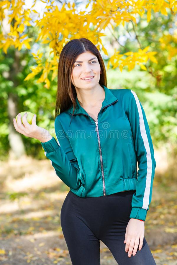 A young girl in a sports suit holds a green apple outdoors. Beautiful sports woman eating fruits. stock photos
