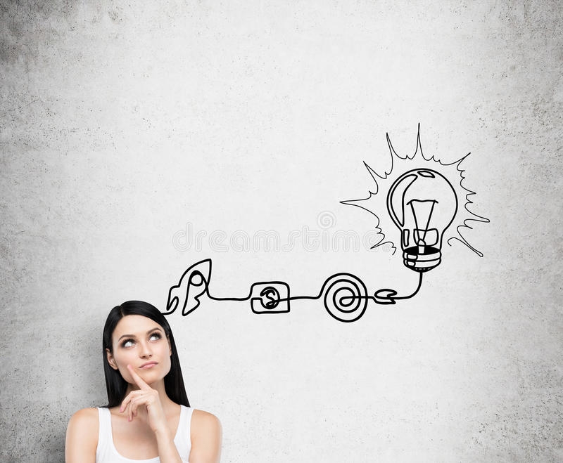 A young brunette lady is thinking about the process of developing a new idea. A flowchart is drawn on the concrete wall with diffe. Rent stages of development. A royalty free stock photo