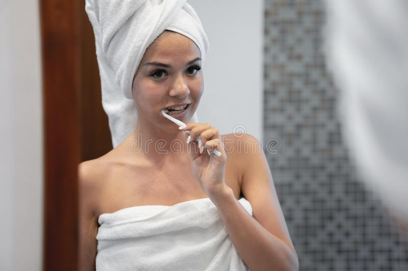 Young brunette looks and cleans teeth. The girl s head and body are dressed in white towels royalty free stock images