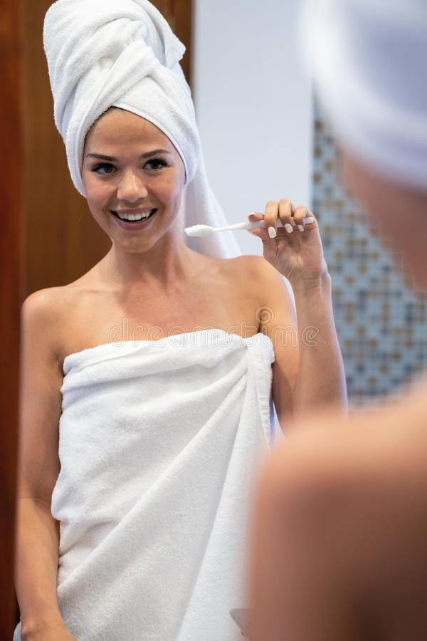 Young brunette looks and cleans teeth. The girl s head and body are wrapped in white towels stock photo