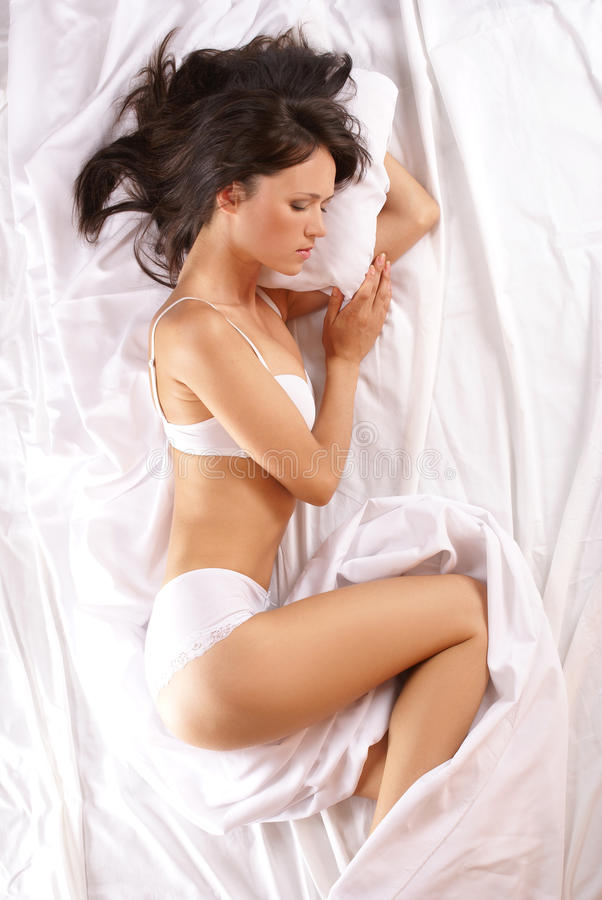 Download A Young Brunette Is Lying On A White Silk Bed Stock Photo - Image: 14077622