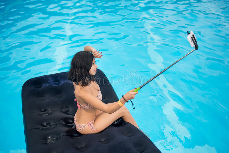 Young brunette makes selfie photo on the phone with selfie stick on mattress in pool. Copy space. View from above stock photography