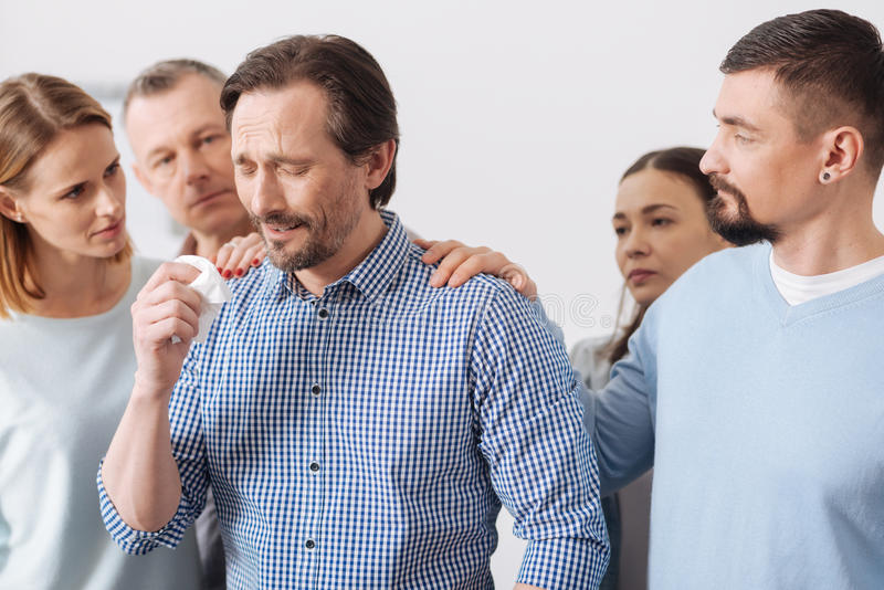 Young brunette male crying while meeting. Cannot believe in such news. Sad bearded men wrinkling his forehead pressing serviette in right hand while standing royalty free stock photos