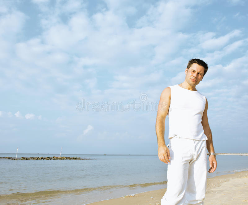 Young brunette man on beach at sea smiling. Gomosexual in white dress big muscles royalty free stock photo
