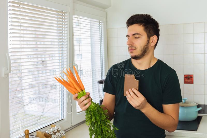 A young brunette man looks at a carrot with disdain and disgust. A person does not lead a healthy lifestyle, he wants to eat sweets and not healthy food stock photos