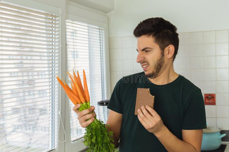 A young brunette man looks at a carrot with disdain and disgust. A person does not lead a healthy lifestyle, he wants to eat sweets and not healthy food stock images