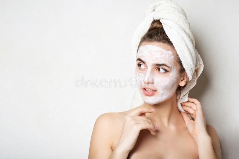 Young brunette model with moisturizing cream mask and bath towel on head. Empty space. Young brunette woman with moisturizing cream mask and bath towel on head royalty free stock photography