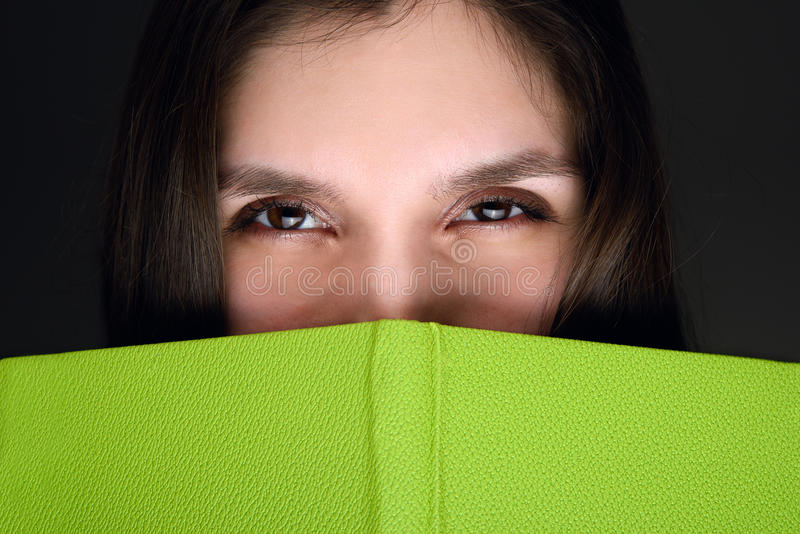 Young brunette model posing with green book covering half her face close-up stock images