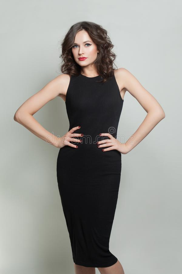 Young brunette model woman wearing black dress standing on white background stock photography