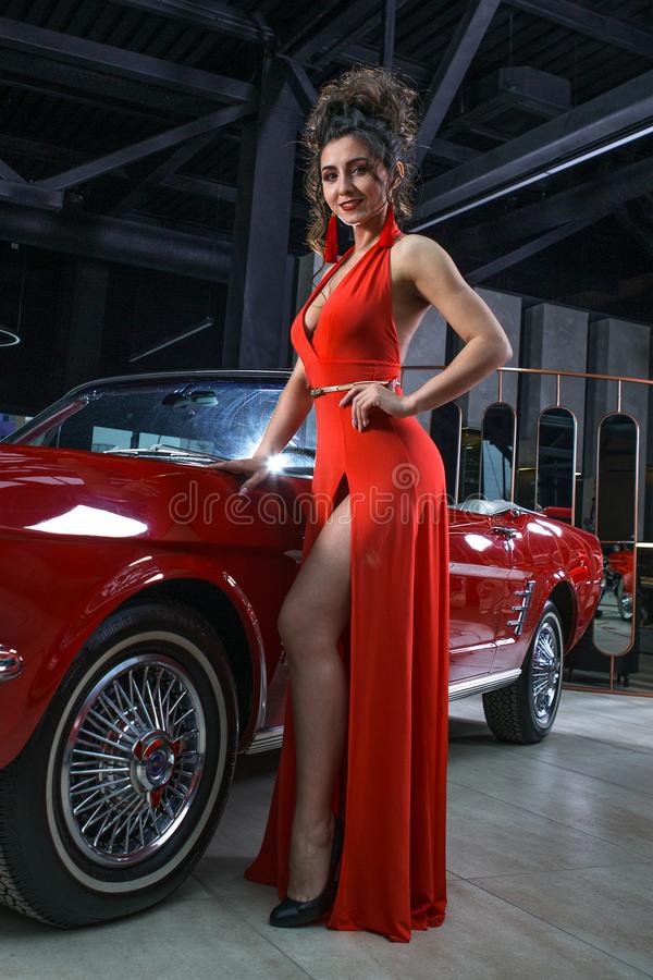 Sexy girl in a red dress posing on a background of red cars royalty free stock images