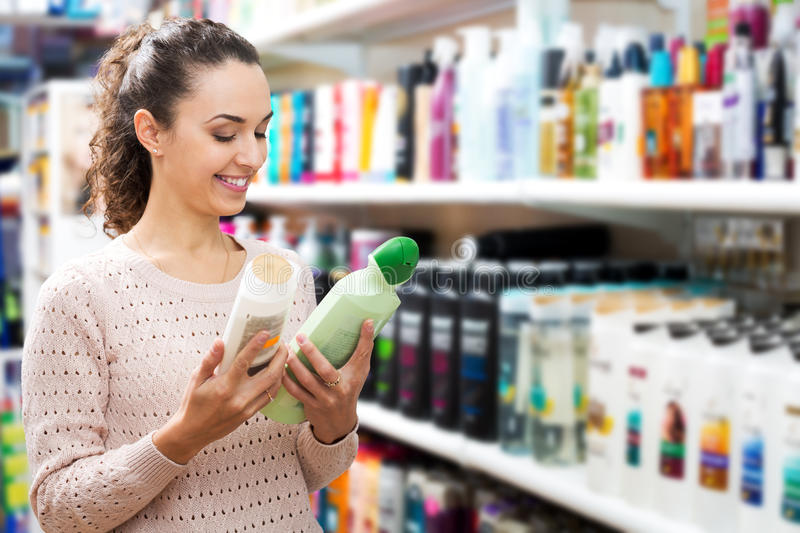 Young brunette selecting bottle of shampoo. Cheerful young brunette selecting bottle of shampoo in beauty store royalty free stock images
