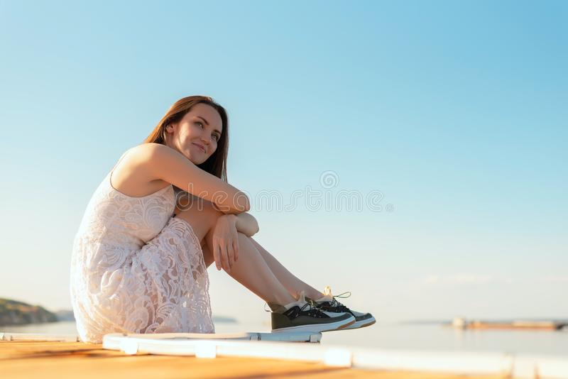 Young brunette sitting on the pier hugging her knees looking at the horizon, smiling at sunset day stock photography