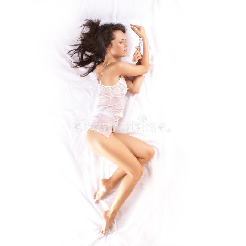 Download A Young Brunette Is Sleeping On White Silk Stock Image - Image: 16848321