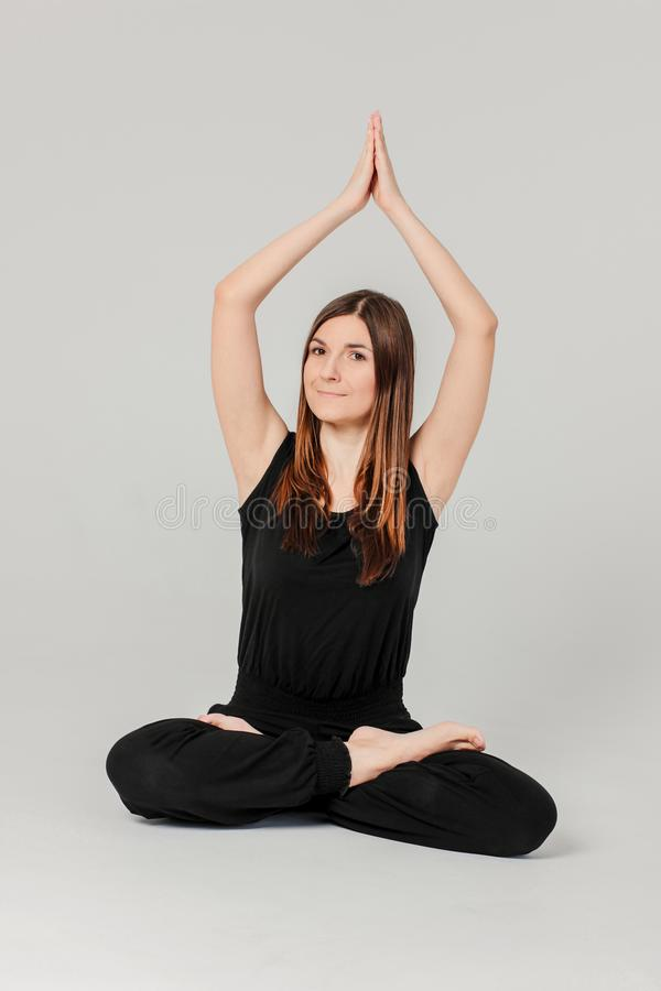 Young brunette slim woman in black sitting in Lotus position in royalty free stock photos