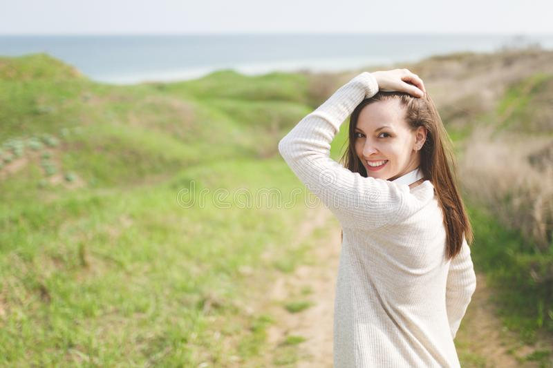 Young brunette smiling beautiful woman in light casual clothes keeping hand near head walking in sunny weather in field. Near water on green background stock photography