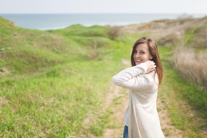 Young brunette smiling beautiful woman in light casual clothes keeping hand near neck walking in sunny weather in field. Near water on green background royalty free stock image