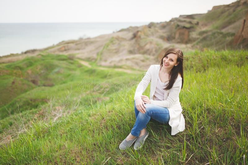Young brunette smiling beautiful woman in light casual clothes sitting on grass with crossed hands and legs near water. On green field background. Beautiful stock image