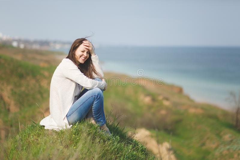 Young brunette smiling pretty woman in light casual clothes sitting on grass keeping hand near head frowning near water. On green field background. Beautiful stock photo
