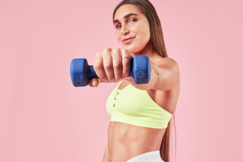 Young brunette smiling sporty woman training with dumm bell in hand, sport outfit on pink background. stock photography