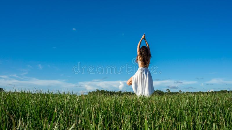 Young brunette spanish woman doing Vriksasana tree yoga pose in a field next to a lake with long curly hair Space in sky stock image