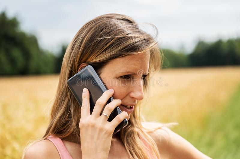 Young brunette talking on her black mobile phone while walking outside stock photos