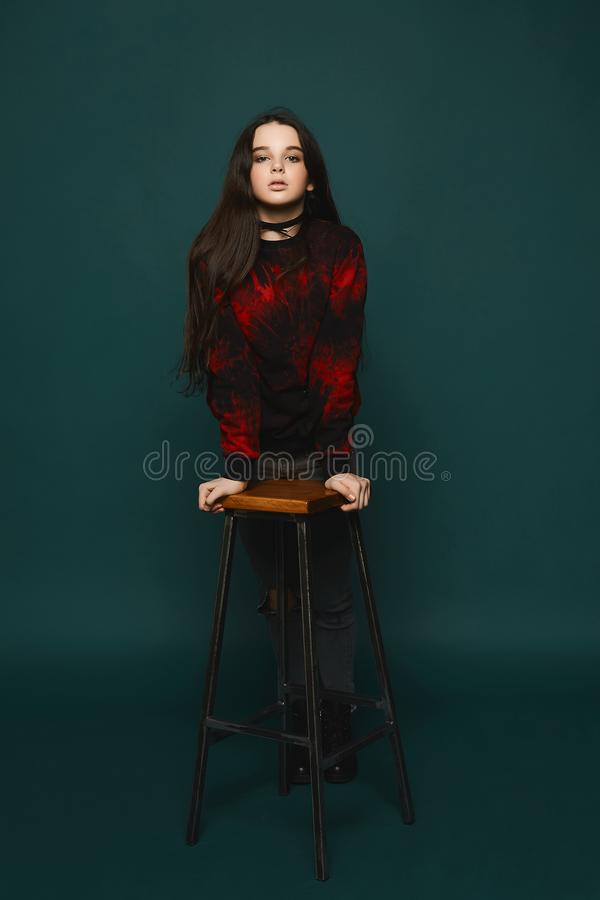 Young brunette teen girl stands near the chair over dark-green background, isolated in studio stock photo