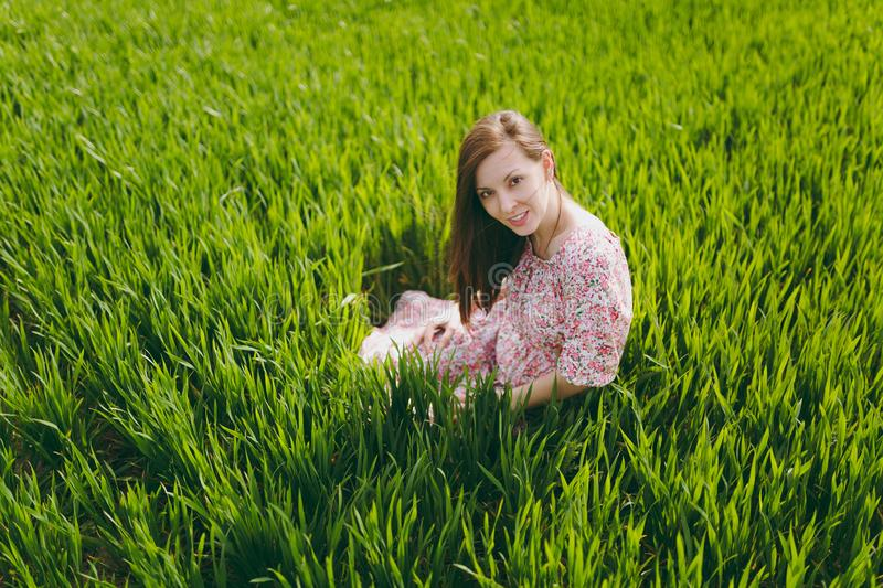Young brunette tender attractive woman in light patterned dress sitting on grass relaxing resting in sunny weather in royalty free stock photography