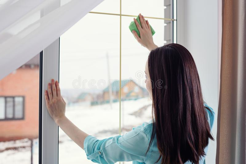 Young brunette washes panoramic window with a cloth of microfiber, without smudges royalty free stock photo