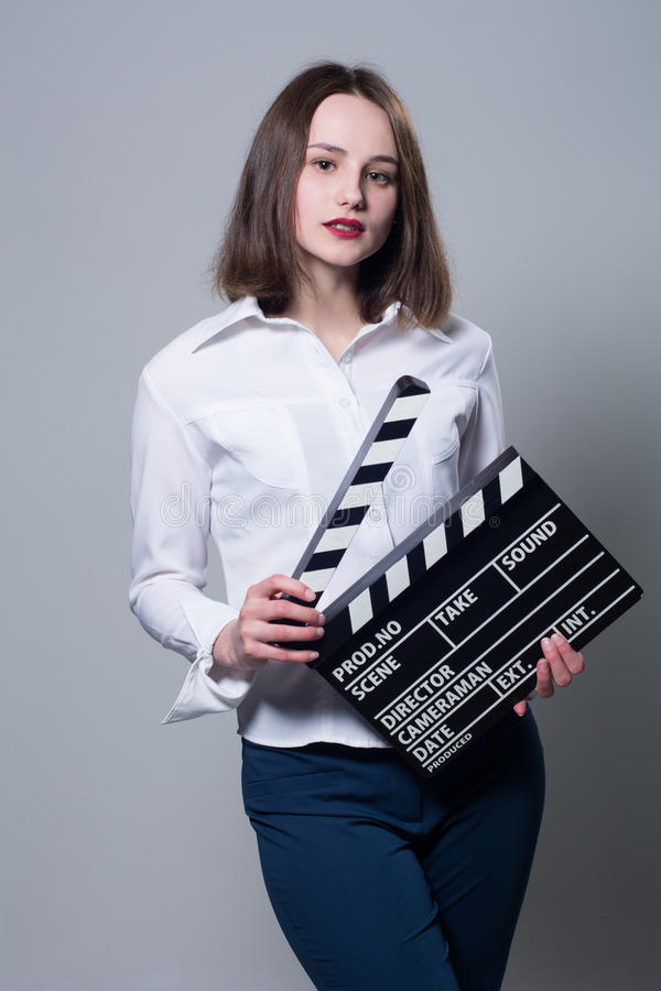 Young brunette in a white blouse with movie cracker. Assistant director with a clapperboard on a gray background royalty free stock photos