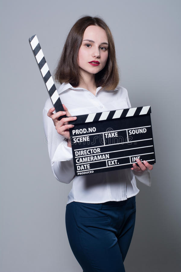 Young brunette in a white blouse with movie cracker. Assistant director with a clapperboard on a gray background royalty free stock photo