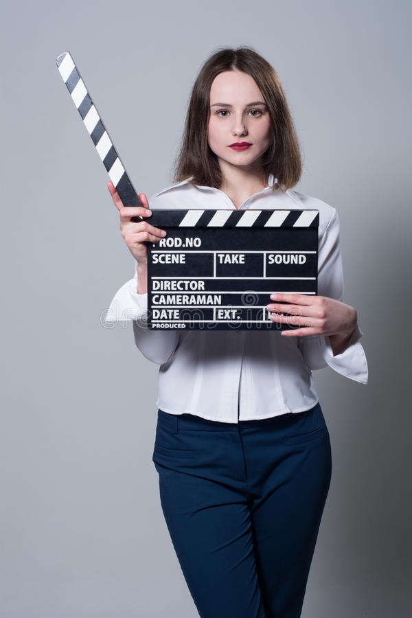 Young brunette in a white blouse with movie cracker. Assistant director with a clapperboard on a gray background royalty free stock image