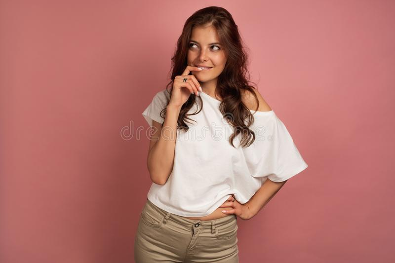 Young dark-haired woman in a white t-shirt and beige pants looks up as she conceives some plan, pink background royalty free stock image