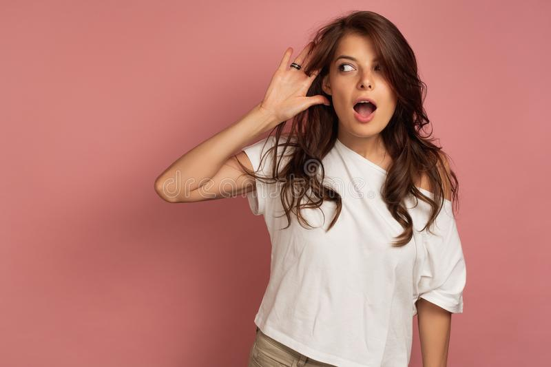 Young brunette in a white t-shirt with open mouth tries to hear something happening far away. Young brunette with open mouth tries to hear something by taking royalty free stock image
