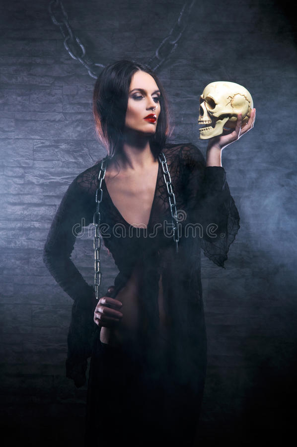 A young brunette witch holding a human skull stock image