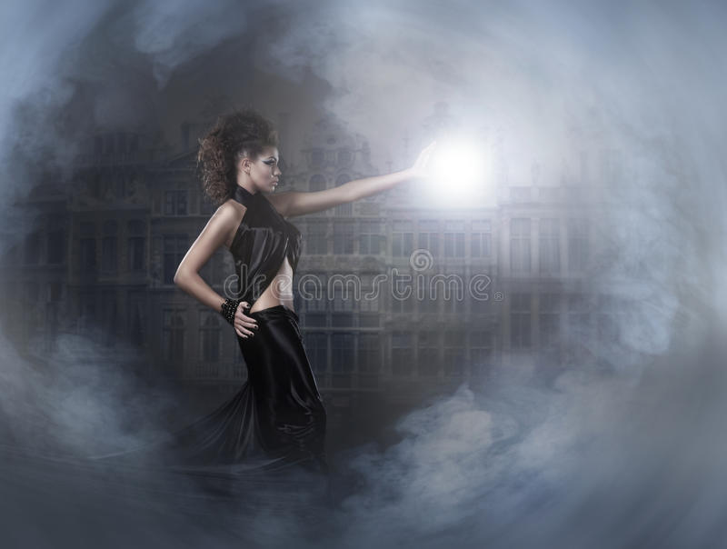 A young brunette wizard casting a lightning ball. Halloween image of a young and attractive brunette female wizard in a dark dress casting a lightning ball. The stock images