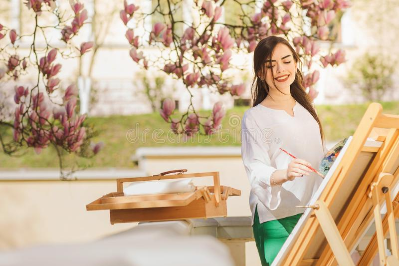 Young brunette woman artist holding in hands a brush and palette. Near her the magnolia tree and various art equipment stock image