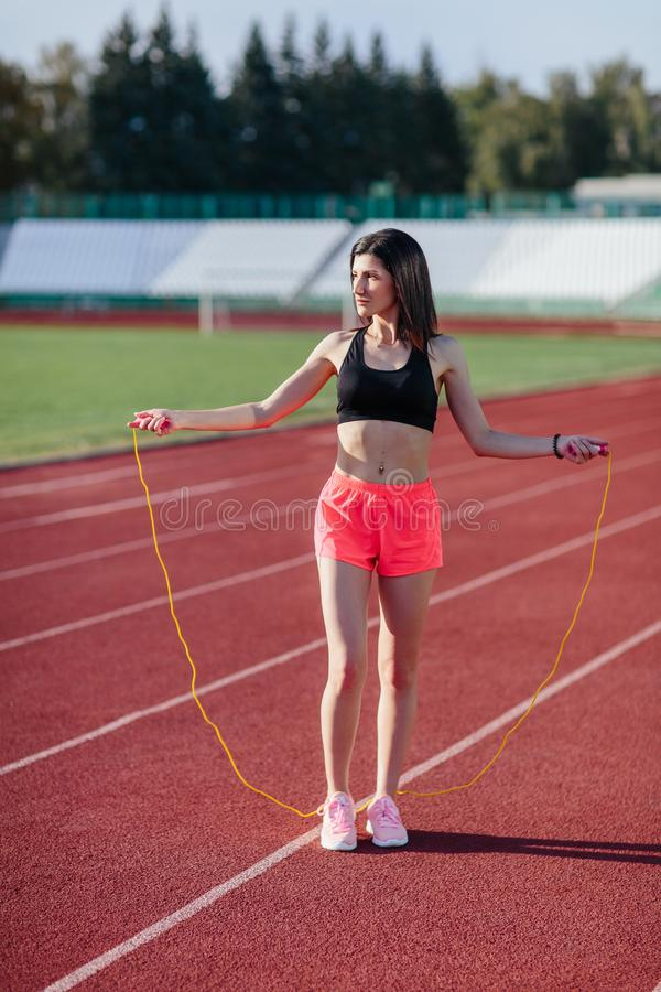 Young brunette woman athlete in pink shorts and black top on stadium sporty lifestyle standing on track holding jump rope under stock image