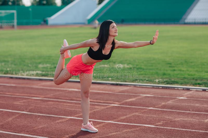 Young brunette woman athlete in pink shorts and top on stadium sporty lifestyle standing stretching leg side view.  stock photo