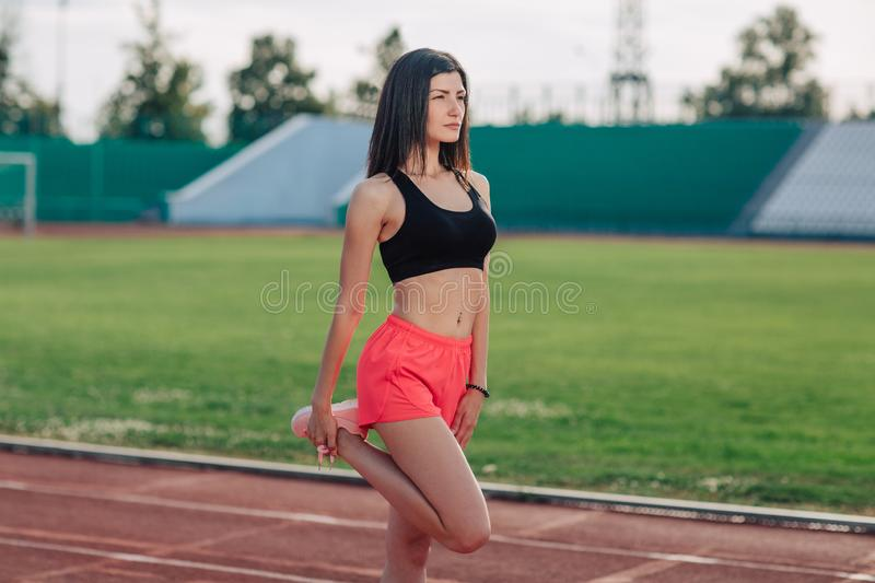 Young brunette woman athlete in pink shorts and top on stadium sporty lifestyle standing stretching leg side view.  stock image