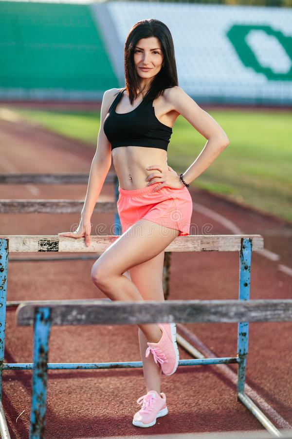 Young brunette woman athlete on stadium sporty lifestyle standing on track posing near the barriers running jumping to camera. Smiling playful royalty free stock photography