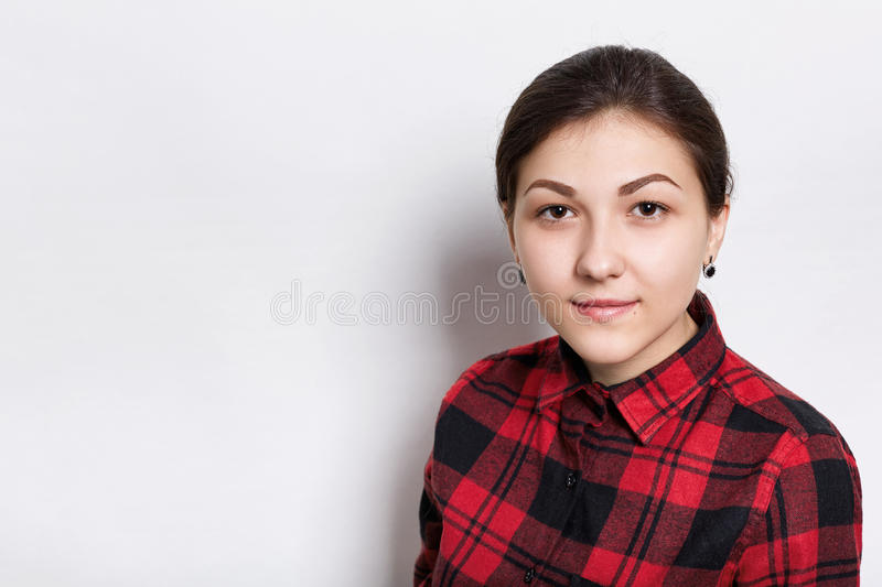 A young brunette woman with braided hair brown eyes and expressive eyebrows dressed in red checked shirt looking serious into came. Ra over white background stock photos