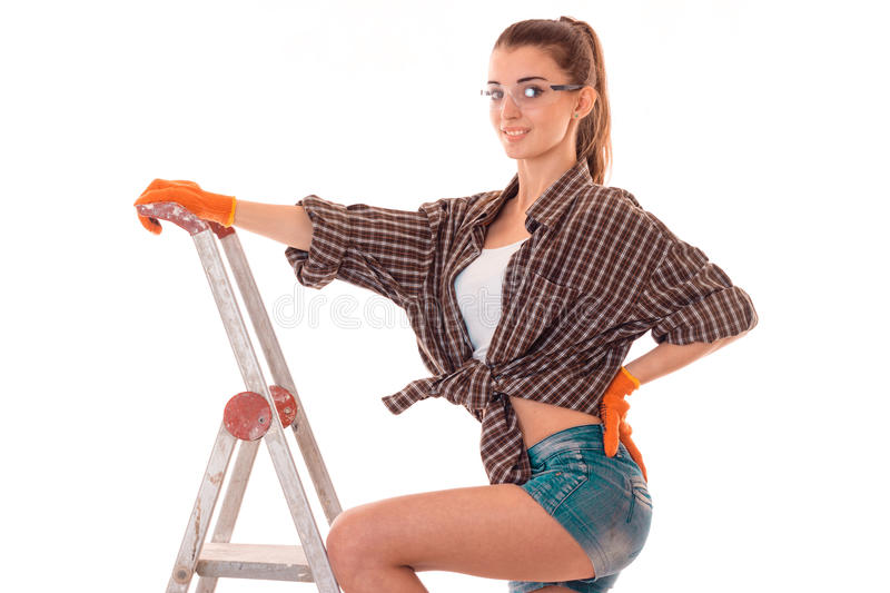 Young brunette woman builder in uniform makes renovations on ladder looking and posing on camera isolated on white royalty free stock image