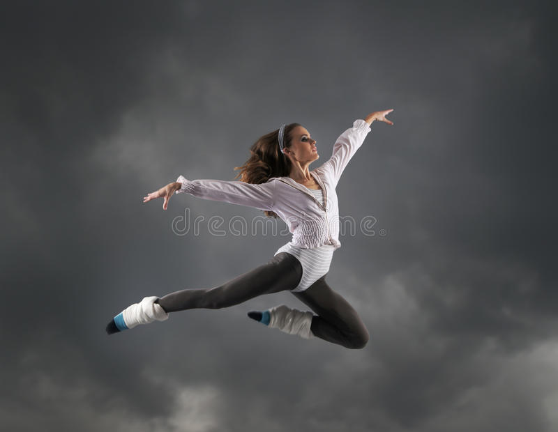 A young brunette woman caught in a jump stock photography