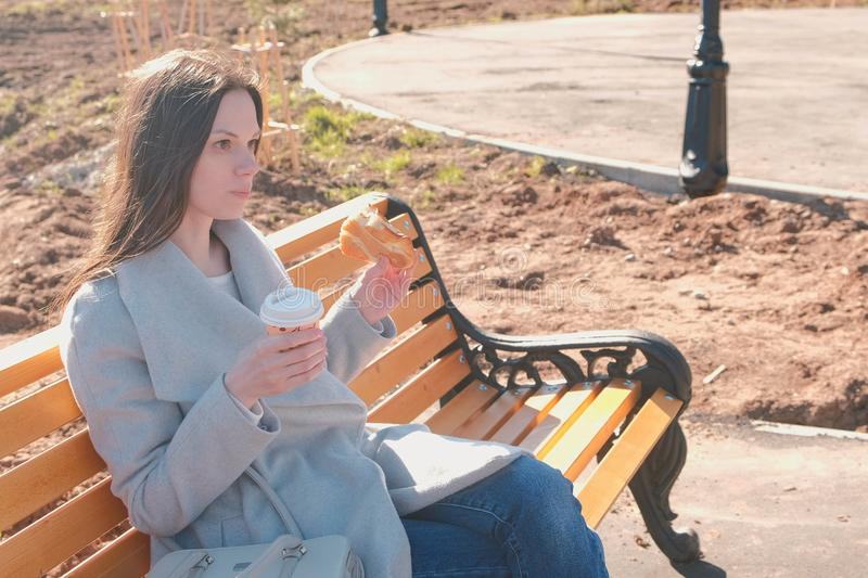 Young brunette woman in coat sits on bench in city park, eats bun with sugar and drinks coffee. Springtime. Young brunette woman in coat sits on bench in city stock image