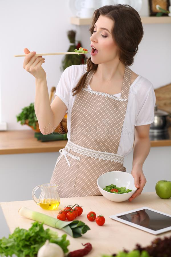 Young brunette woman cooking in kitchen. Housewife holding wooden spoon in her hand. Food and health concept royalty free stock photo