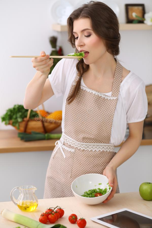 Young brunette woman cooking in kitchen. Housewife holding wooden spoon in her hand. Food and health concept.  royalty free stock images